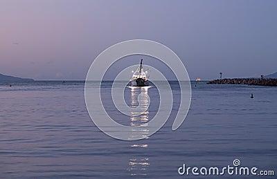Barco de pesca que sae do alvorecer do porto de Ventura