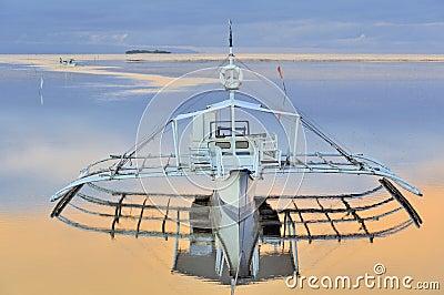 Barco del soporte en el océano tranquilo hermoso en la salida del sol