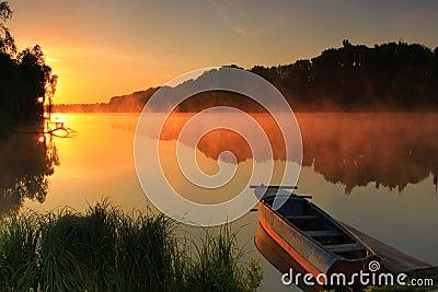 Barco na costa de um lago enevoado