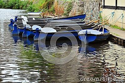 Barcos do aluguer na superfície do rio com reflexões