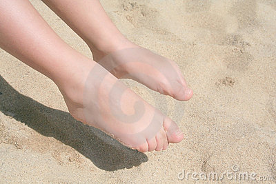 Bare feet of child on sand,