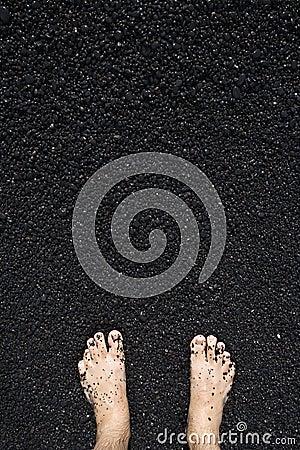 Barefeet in black sand