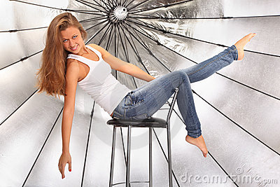 Barefoot girl sits on chair near umbrella