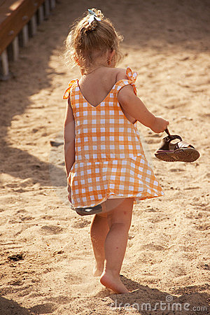 Barefoot little girl walking on beach