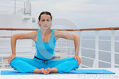 Barefoot woman sits and does exercise