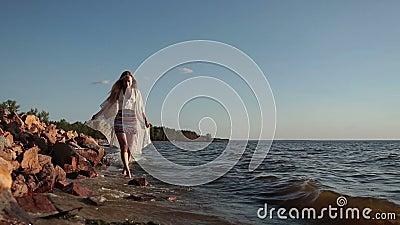Barefoot woman walking on seaside at golden sunset stock video