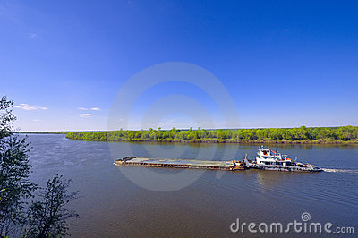 The barge with cargo on river in sunny day