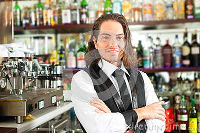 Barista or barman behind his bar