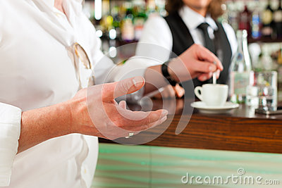 Barista with client in his cafe or coffeeshop