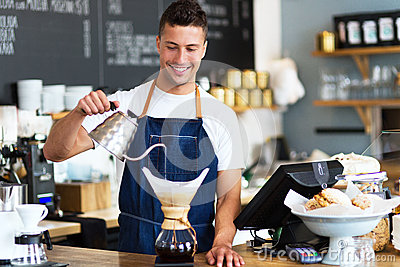 Barista pouring water into coffee filter Stock Photo