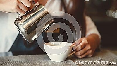 Barista professionnelle asiatique versant du lait dans du café d'art latte au comptoir-bar de la cafétéria restaurant en tant que clips vidéos