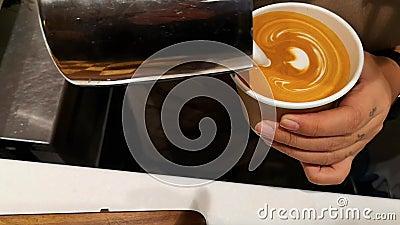 Barista som gör av kafélattekonst, läckert kaffe med en liten hjärtaform stock video