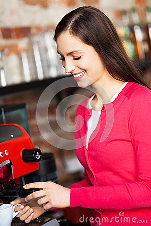 Female barista by coffee maker