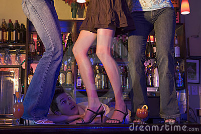 Barman gaping at three young women dancing on bar