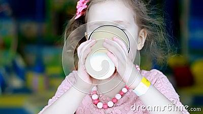 Barn dricker kaffe Nära porträtt av en söt flicka som dricker en drink stock video
