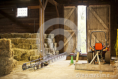 Barn interior with hay bales and farm equipment