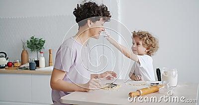 Barn som har kul med att laga mat med moder som rör näsan med smutsigt finger. stock video