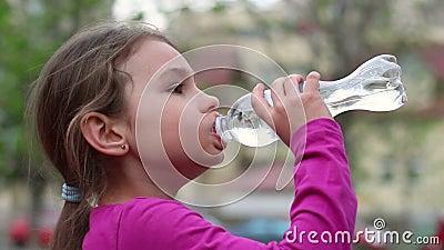 Barndricksvatten från den utomhus- flaskan Ung flicka med vattenflaskan i hand