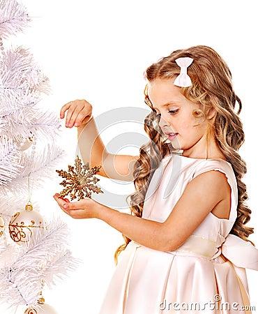 Barnet dekorerar julgranen.