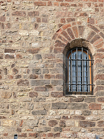 Barred window in stone wall