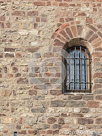 Barred window in stone wall