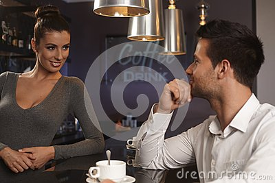 Bartender flirting with young man in bar