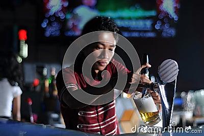Bartender poring beer