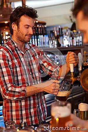 Bartender serving draught beer in bar