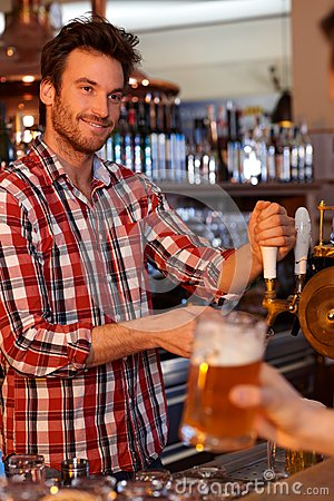 Bartender tapping fresh beer in bar