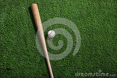 Baseball bat and ball on green turf background
