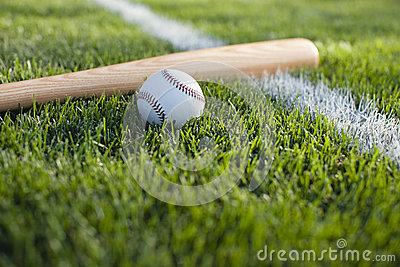 Baseball and bat in grass on a stripe