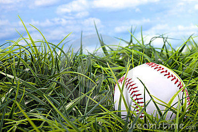 Baseball in grass with blue sky and white clouds