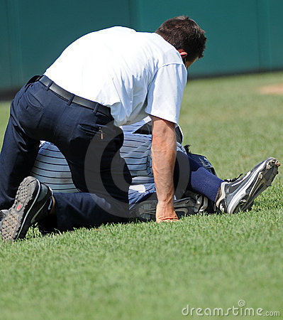 Baseball injury - trainer tends to player Editorial Photo