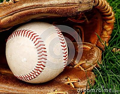 Baseball with mitt in grass