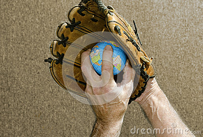 Baseball pitcher holding world globe in glove