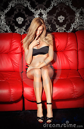 Bashful young blonde lady on red leather sofa