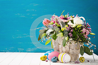 Basket of flowers and easter eggs on a wooden background Stock Photo