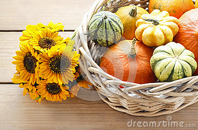Basket of pumpkins on wooden table