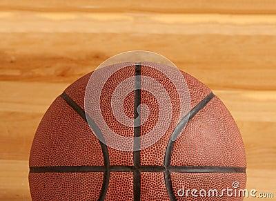 Basketball on floor of hard wood court