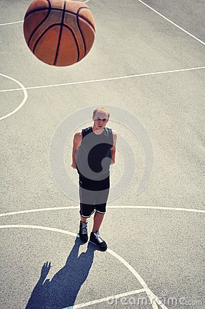 Basketball player at the court shooting the ball
