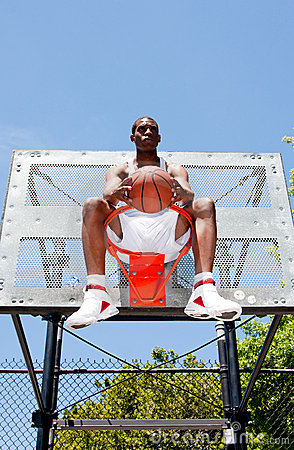 Basketball player sitting in hoop