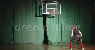 Basketbalspeler kijkt krullend naar de mand om te zien hoe de bal alleen vertrouwt als hij lichtbundeltrainingen volgt stock footage