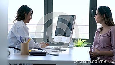 Bastante joven ginecóloga revisando la historia médica de su paciente embarazada con computadora en la clínica. almacen de metraje de vídeo