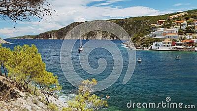 Bateau à voile dans la baie de mer en été La Grèce côtoie le village et la côte de l'île de Kefalonia en arrière-plan clips vidéos