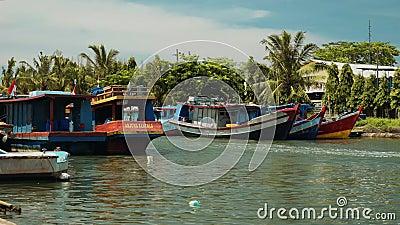 Bateaux de pêche naviguant en rivière dans Cilacap, Java, Indonésie banque de vidéos