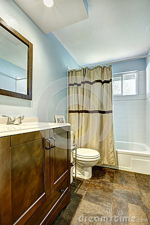 Bathroom With Brown Tile Floor And Light Blue Walls Stock