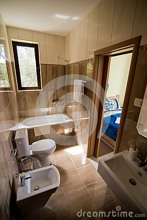 Free Bathroom Interior - Washbasin, Bidet, Toilet, Large Mirror. The Walls Are Light Brown In Color. Stock Photography - 90802502