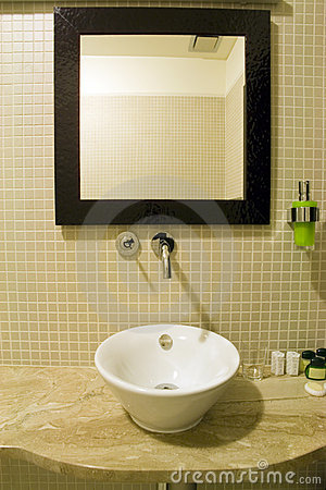 view focusing on a unique bathroom sink and mirror with black frames