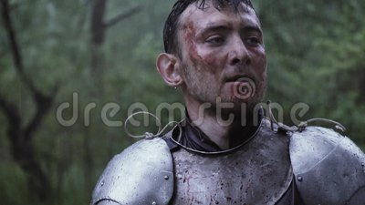 Knight with dirt and blood on his face is looking around after the battle. After the battle in the forest under the rain, a knight in metal armor is looking stock video footage