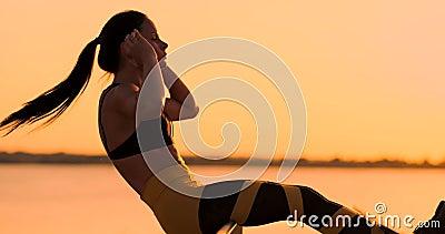 Bauchmuskel?bungen Eine junge Schönheit athletisch bei Sonnenuntergang gegen den See in der Sommerfrau beim Sportkleidungshandeln stock footage